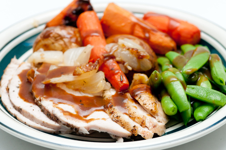 smothered: traditional turkey dinner with crispy skin, turkey slices and fresh roasted  vegetables smothered in gravy Stock Photo