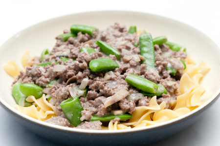 ground beef: ground beef hamburger stroganoff with chopped snap peas and broad egg noodles in a mushroom sauce