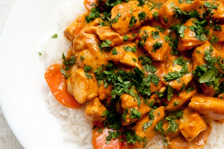 human meat: chicken korma, a spicy Indian themed meal of diced chicken, rice and creamy korma sauce topped with chopped cilantro