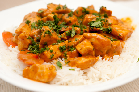 vegetable curry: chicken korma, a spicy Indian themed meal of diced chicken, rice and creamy korma sauce topped with chopped cilantro