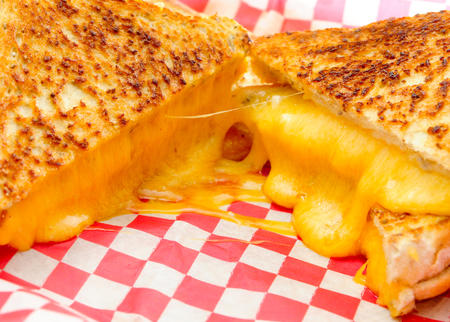 melted cheese: decadent grilled cheese sandwiches with oozing cheese running out with ketchup for dipping