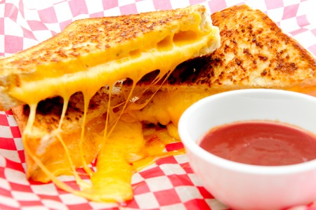 decadent: decadent grilled cheese sandwiches with oozing cheese running out with ketchup for dipping