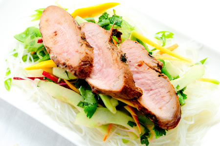grilled pork tenderloin with fresh sauteed vegetables over mango and glass noodles