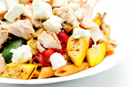 primavera: chicken pasta penne primavera, a delicious heart healthy vegetable and chicken dish topped with fresh goat cheese Stock Photo