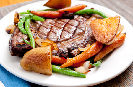 ethically raised, fresh cut organic rib eye steak grilled rare with fresh roasted vegetables