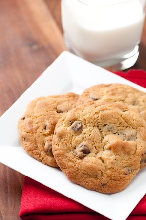 semisweet: oven fresh home made chocolate chip and walnut cookies with a glass of milk