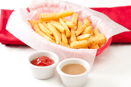 fatty food: crispy crinkle cut french fries with gravy and ketchup Stock Photo