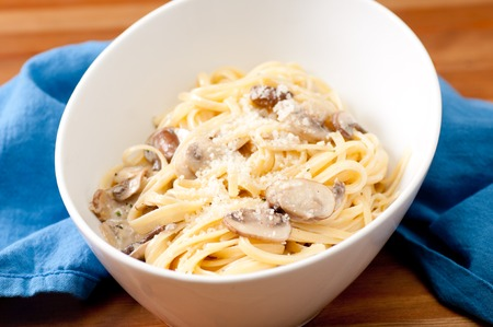 button mushroom: linguine pasta with creamy alfredo sauce with parmesan and crimini mushrooms Stock Photo