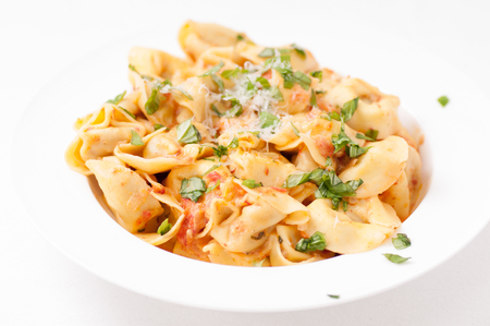 stuffed tortellini: tortellini stuffed with cheese in a creamy tomato and parmesan  cheese sauce Stock Photo