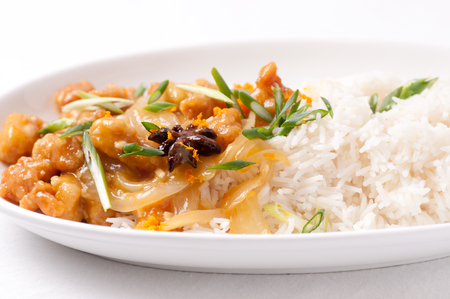 tangy: spicy and tangy chicken glazed with orange over white rice with onion