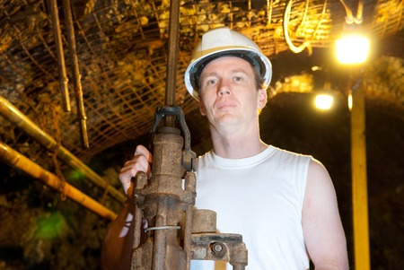 the miner: Underground miner drilling into rock for copper