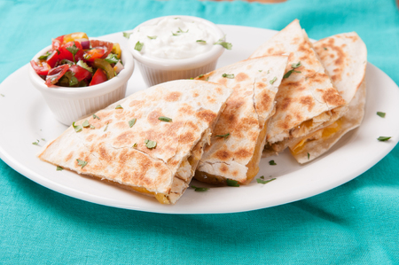 tex mex: homemade quesadilla with chicken and hand made salsa plus yogurt and sour cream Stock Photo