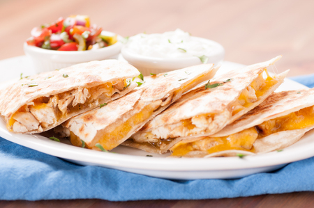 flavorsome: homemade quesadilla with chicken and hand made salsa plus yogurt and sour cream Stock Photo