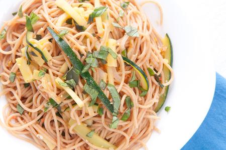 lactose intolerant: vegan zucchini pasta over gluten free noodles with tomato Stock Photo