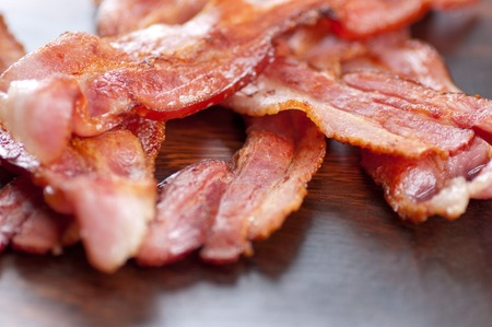bacon fat: crispy sliced ethically raised organic bacon on a wooden plate