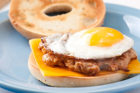 sunnyside: fried sunnyside up egg on a sausage patty with a bagel and cheese