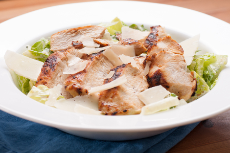 ensalada cesar: caesar salad topped with grilled chicken and shaved parmesan cheese