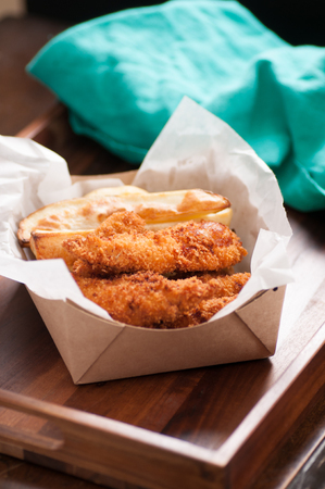 take out: breaded chicken fingers and fries in a take out container Stock Photo