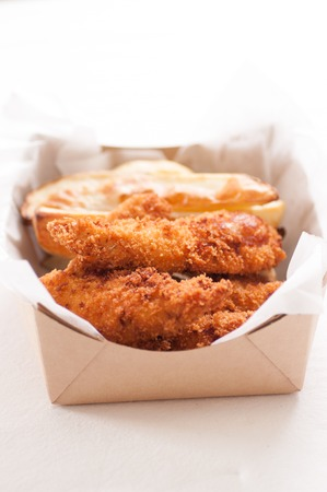 chicken fingers: breaded chicken fingers and fries in a take out container Stock Photo
