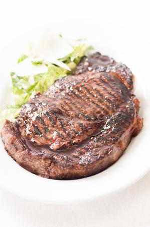 a rare: thick ribeye steak seared rare on a cast iron grill