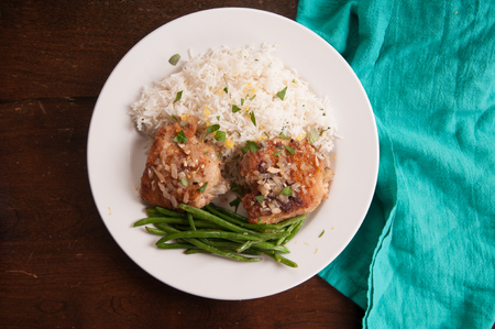 muslos: cripsy fried chicken thighs with vegetables over rice in a lemon sauce Foto de archivo