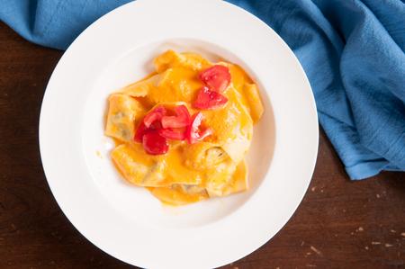 raviolo: delicious stuffed mezzaluna pasta made from scratch with heirloom tomato sauce Stock Photo