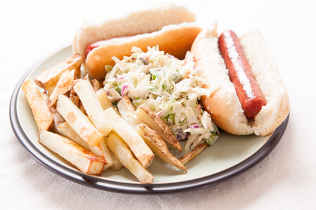 cole: grilled hot dogs on fresh buns with hand cut fries and tasty cole slaw Stock Photo