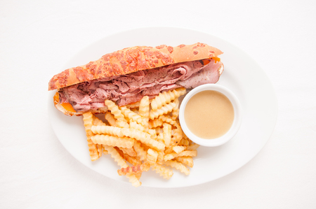deli: deli style sliced rare roast beef on a cheese bun with french fries and gravy Stock Photo