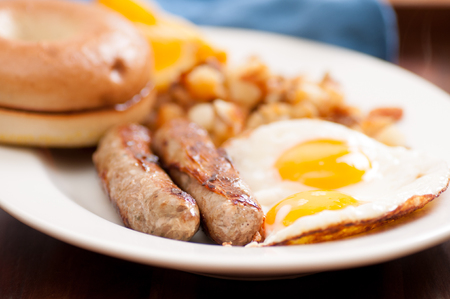 sunny side: sunny side up eggs with english banger sausages and hashbrowns and a bagel