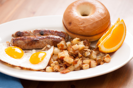 sunnyside: sunny side up eggs with english banger sausages and hashbrowns and a bagel