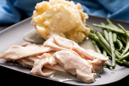 smothered: traditional turkey dinner with crispy skin, turkey slices and fresh roasted vegetables smothered in gravy perfect for Christmas dinner and Thanksgiving meals Stock Photo