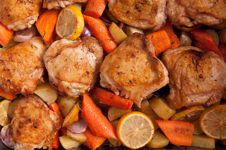 muslos: a roasting pan full of crsipy chicken thighs and vegetables