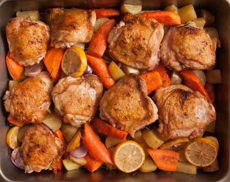 roasting pan: a roasting pan full of crsipy chicken thighs and vegetables