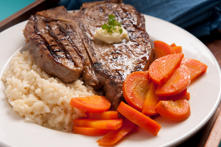 tbone: organic t-bone beef steak done rare with risotto and carrots Stock Photo