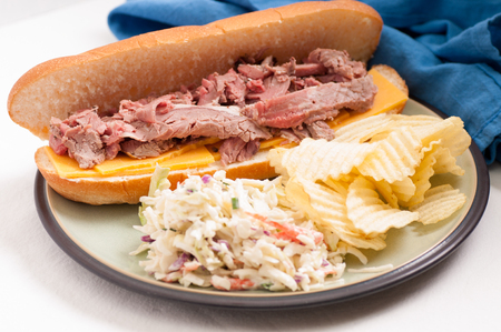 cole: deli style sliced rare roast beef on a roll with cheese, cole slaw and chips