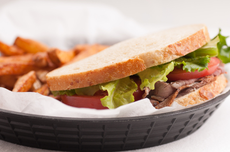 hero sandwich: home made roast beef sandwich on sourdough bread with crispy french fries Stock Photo