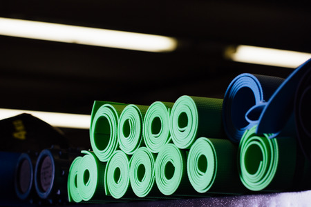 Many yoga mats green and blue colors on the shelf.