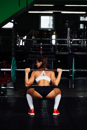 Beautiful fitness woman lifting barbell. Sporty woman lifting weights. Fit girl exercising building muscles. Fitness and bodybuilding. Back view.