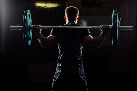 Handsome weightlifter training. Confident muscular man training squats with barbells over head. Closeup portrait of professional bodybuilder workout with barbell at gym. Back view, Silhouette.