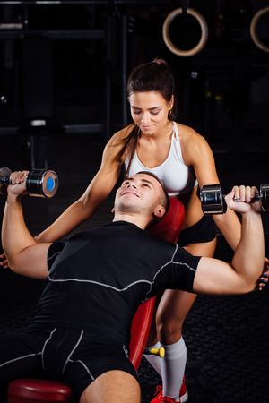 Female personal fitness instructor helping a young man at gym, he exercising with dumbbells on the bech. Stock Photo