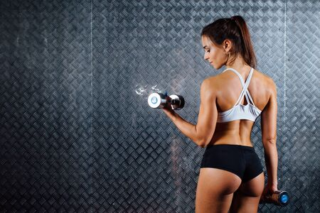 Attractive fitness woman with dumbbell indoor portrait, trained female body, studio caucasian model. Grey metal surface with a bumpy pattern background. Stock Photo