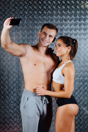Attractive fitness couple in sports clothes is making selfie indoor , trained female body, studio caucasian model. Grey metal surface with a bumpy pattern background.