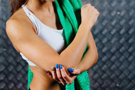 Beautiful young woman feeling pain in her elbow, hand. during sport workout indoors, close-up. Grey metal surface with a bumpy pattern background. Stock Photo