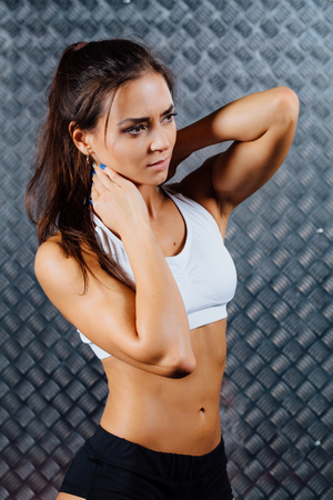 Beautiful young woman feeling pain in her neck during sport workout indoors, close-up. Grey metal surface with a bumpy pattern background.