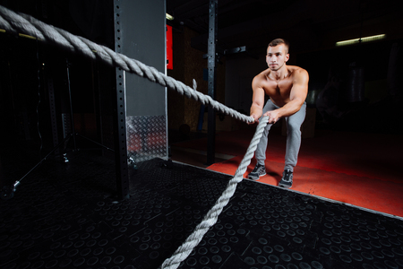 Men with battle rope in functional training fitness gym. Fitness sport.