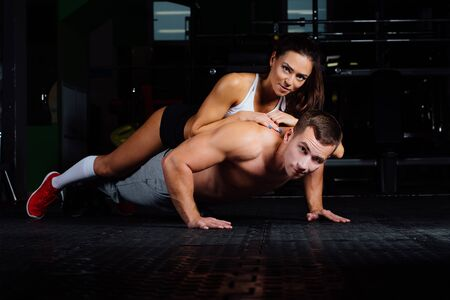 Fit man doing push-ups with woman on back. healthy couple, workout with own body weight, indoor lie , rest.