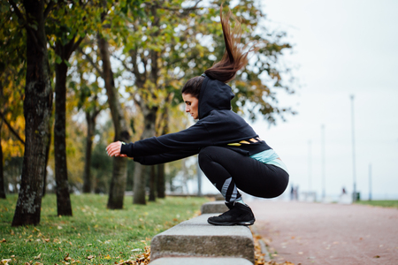 Wman in functional training outdoor at park doing fitness exercise. Sporty girl doing jumps.