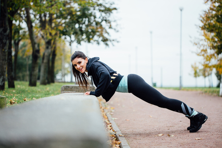 Portrait of woman in sportswear, doing fitness push-ups exercise at fall park, outdoor. Healthy lifestyle, weight lossing and sporting theme concept shot. Biceps dips.looking at the camera, smiling.