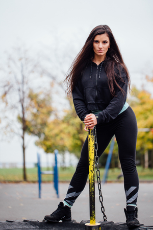 Girl posing at park with hammer and tractor tire. Beautiful brunette sportsgirl workout with sledgehammer. Fitness concept and functional training. Stock Photo