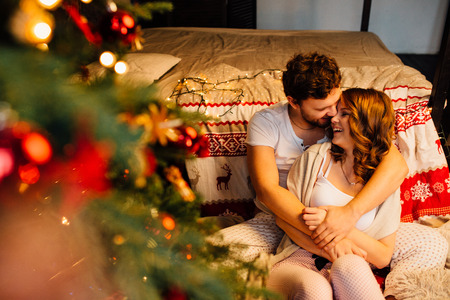 Couple in in pajamas resting on the floor next to the bed near the Christmas tree. The lights garlands, bokeh. Embrace Christmas atmosphere and comfort